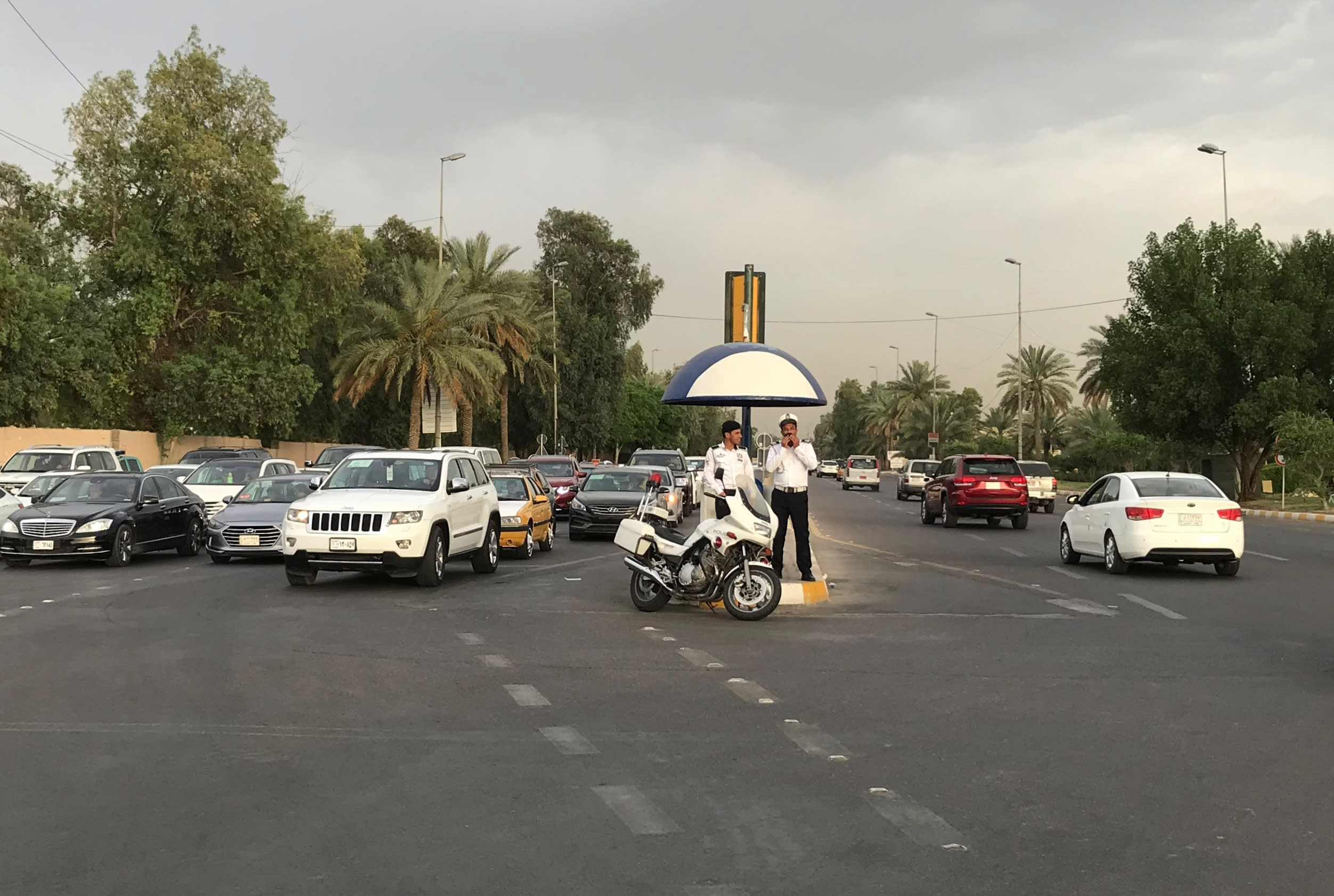 In this Tuesday, May 28, 2019 photo, Iraqi traffic police officers stand at a busy intersection inside the Green Zone in Baghdad, Iraq. The zone has been a barometer for tension and conflict in Iraq for nearly two decades. The sealed-off area, with its palm trees and monuments, is home to the gigantic U.S. Embassy in Iraq, one of the largest diplomatic missions in the world. It has also been home to successive Iraqi governments and is off limits to most Iraqis. (AP Photo/Ali Abdul Hassan)