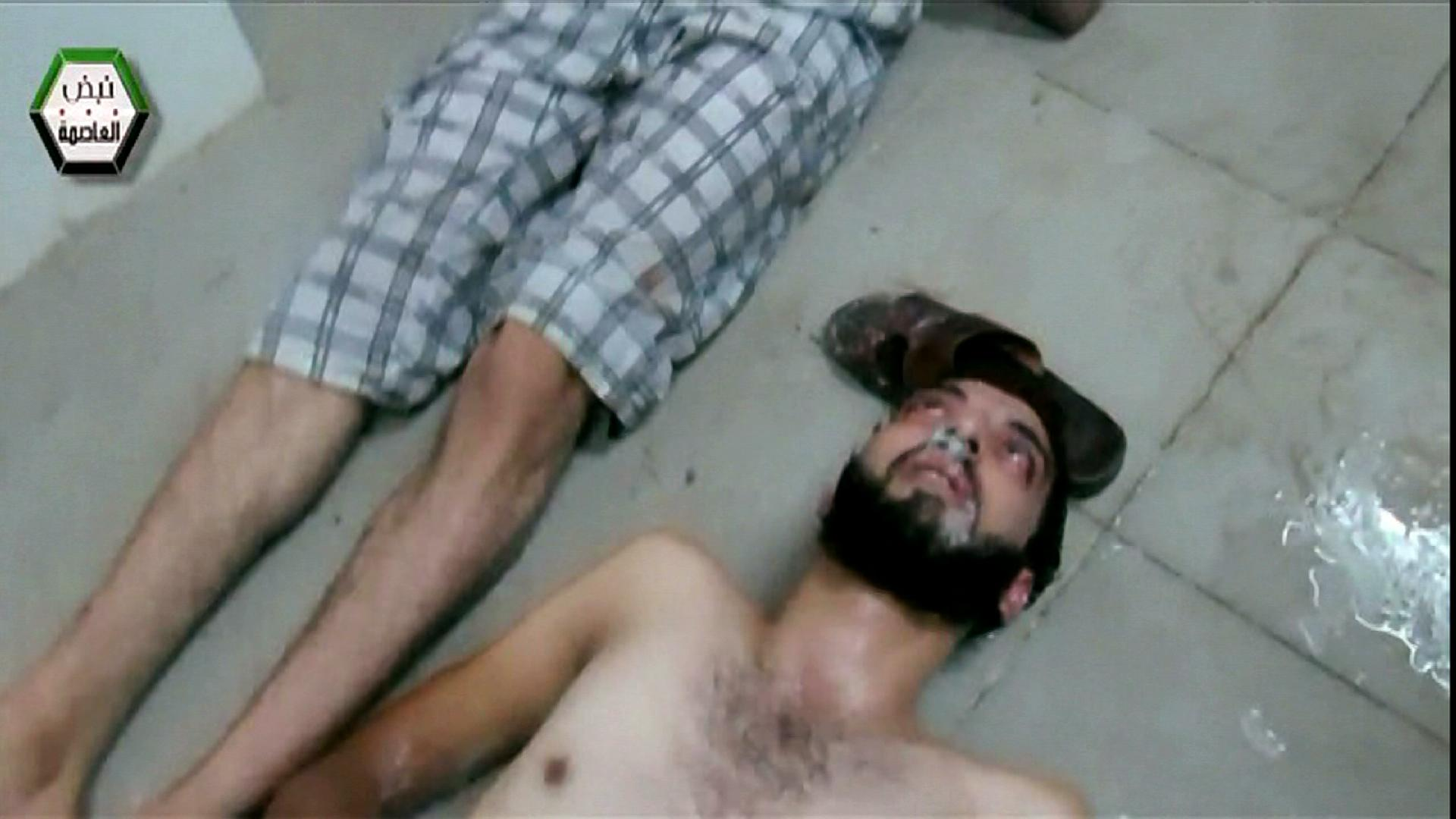 This image from video that was released by a U.S. government official and shown to senators during a classified briefing on Thursday, Sept. 5, 2013, shows a man foaming at the mouth, lying on the floor of a large room with many other people apparently struggling with symptoms of nerve agent exposure in Eastern Gutah in Damascus, Syria. The video was part of a DVD compilation of videos showing victims of the Aug. 21 chemical weapons attack near Damascus. (AP Photo/APTN)