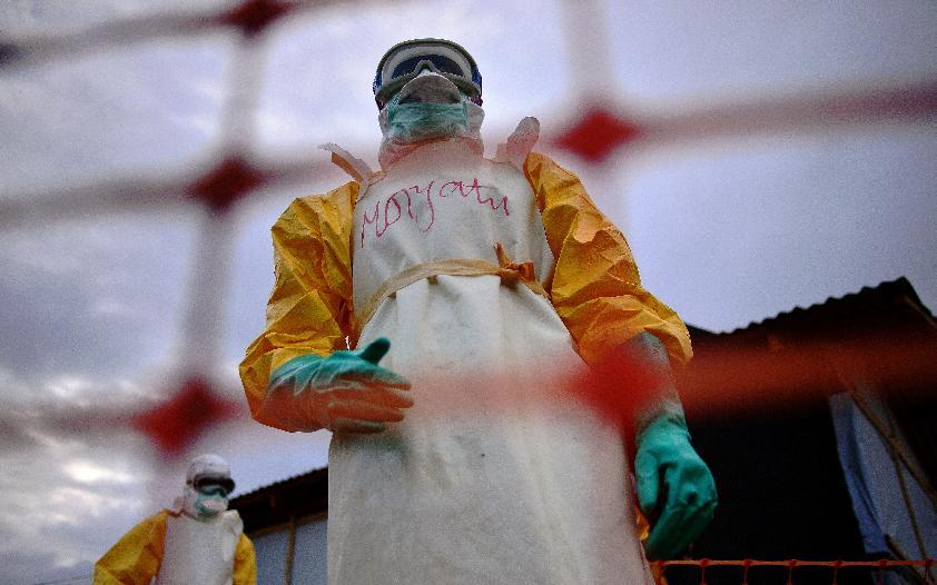 Medical staff wearing protective clothing treat the body of an Ebola victim at their facility in Kailahun, on August 14, 2014 (AFP Photo/Carl de Souza)
