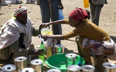 A man receives cooking oil at an emergency food aid distribution in the village of Estayish in Ethiopia's northern Amhara region