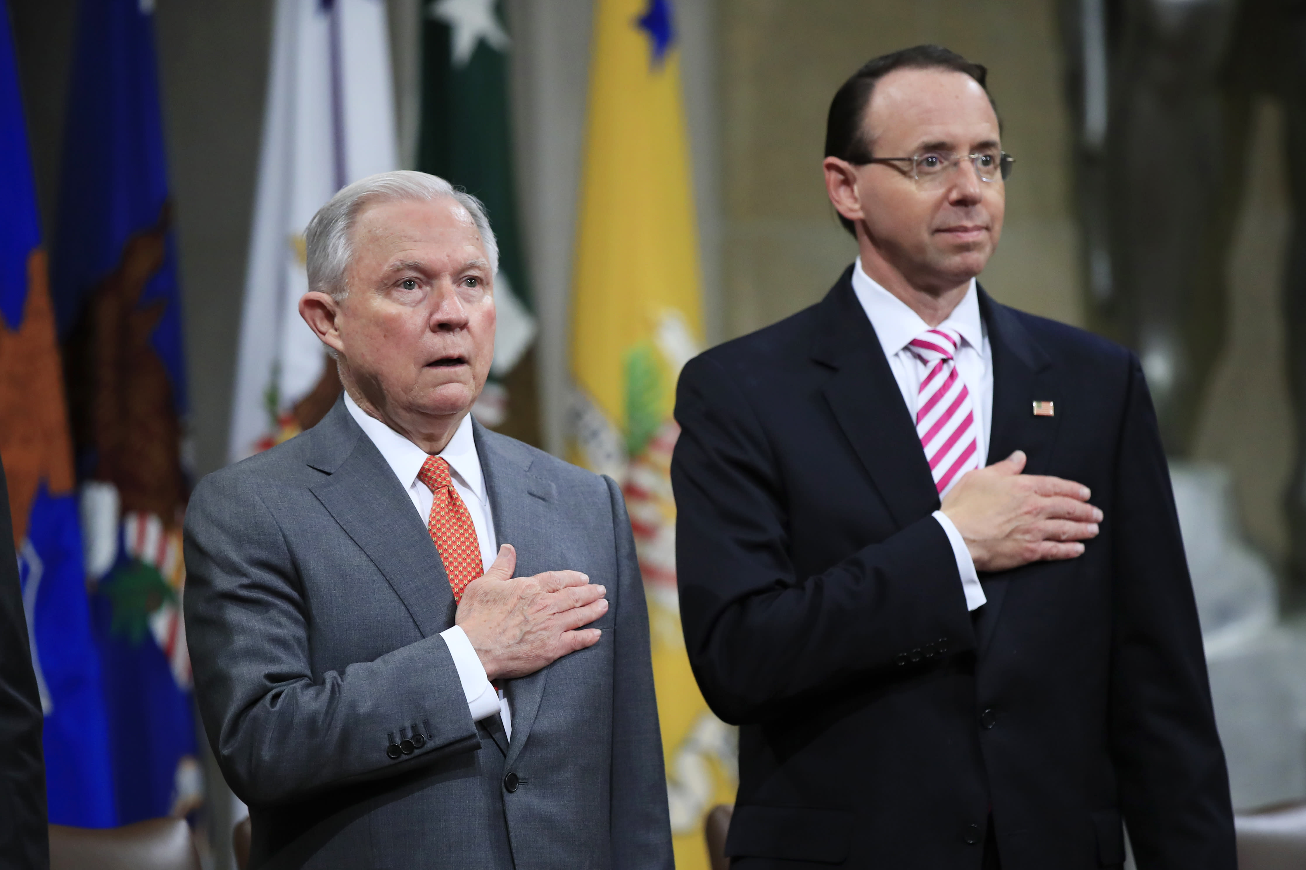 "Attorney General Jeff Sessions, left, and Deputy Attorney General Rod Rosenstein, put their hands over their heart as they sing the National Anthem during a Religious Liberty Summit at the Department of Justice, Monday, July 30, 2018. Sessions says there's a ""dangerous movement"" to erode protections for Americans to worship and believe as they choose. (AP Photo/Manuel Balce Ceneta)"