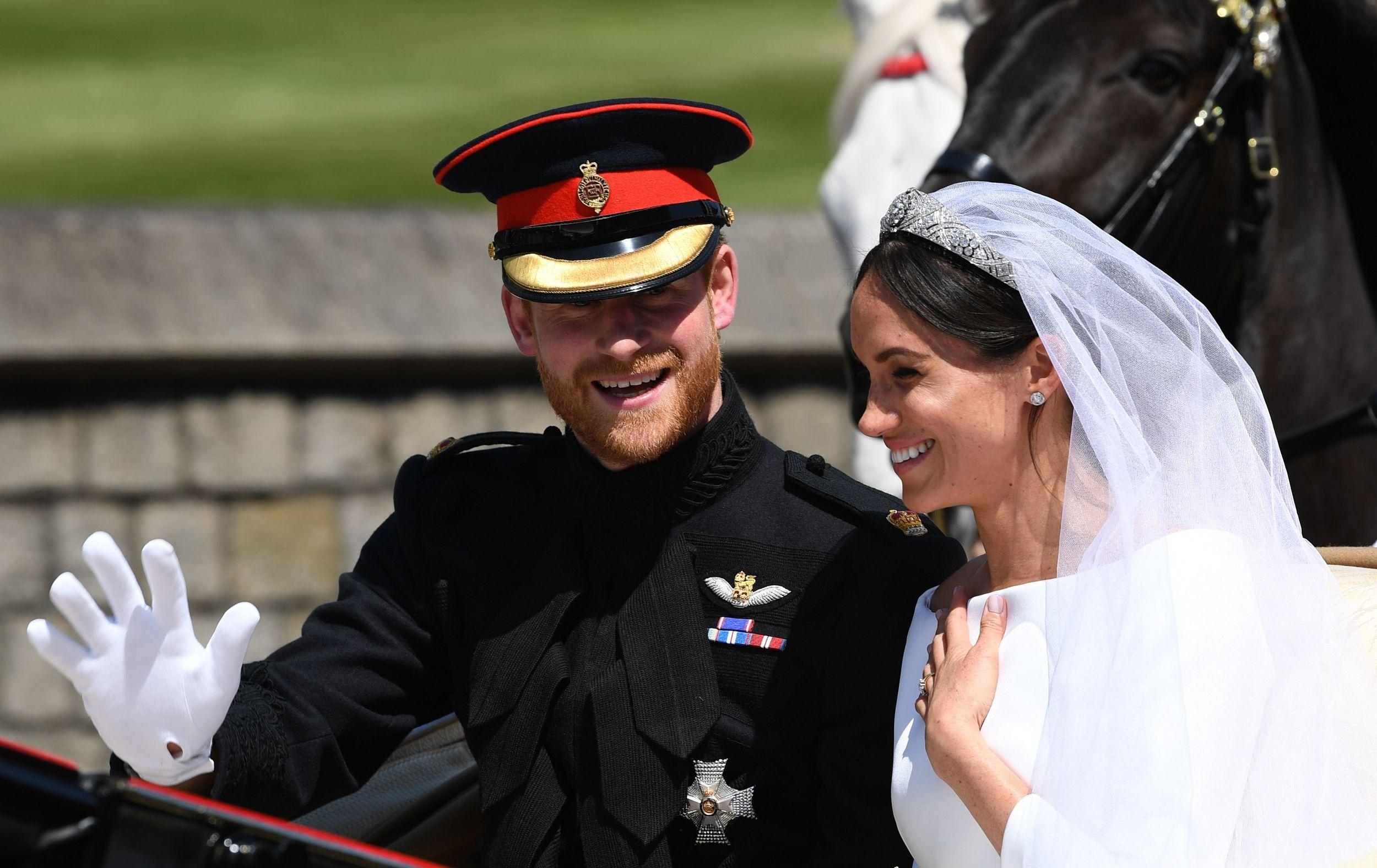 <p>Britain's Prince Harry, Duke of Sussex and his wife Meghan, Duchess of Sussex wave from the Ascot Landau Carriage during their carriage procession on Castle Hill outside Windsor Castle in Windsor, on May 19, 2018 after their wedding ceremony.</p>  <p>(Photo by Paul ELLIS / POOL / AFP)</p>