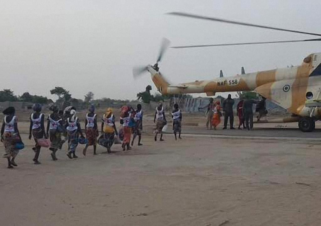 This handout image provided by the International Committee of the Red Cross (ICRC) on May 7, 2017 at a military base in Borno State shows some of the 82 rescued Chibok girls heading towards a Nigerian Army helicopter (AFP Photo/STR)