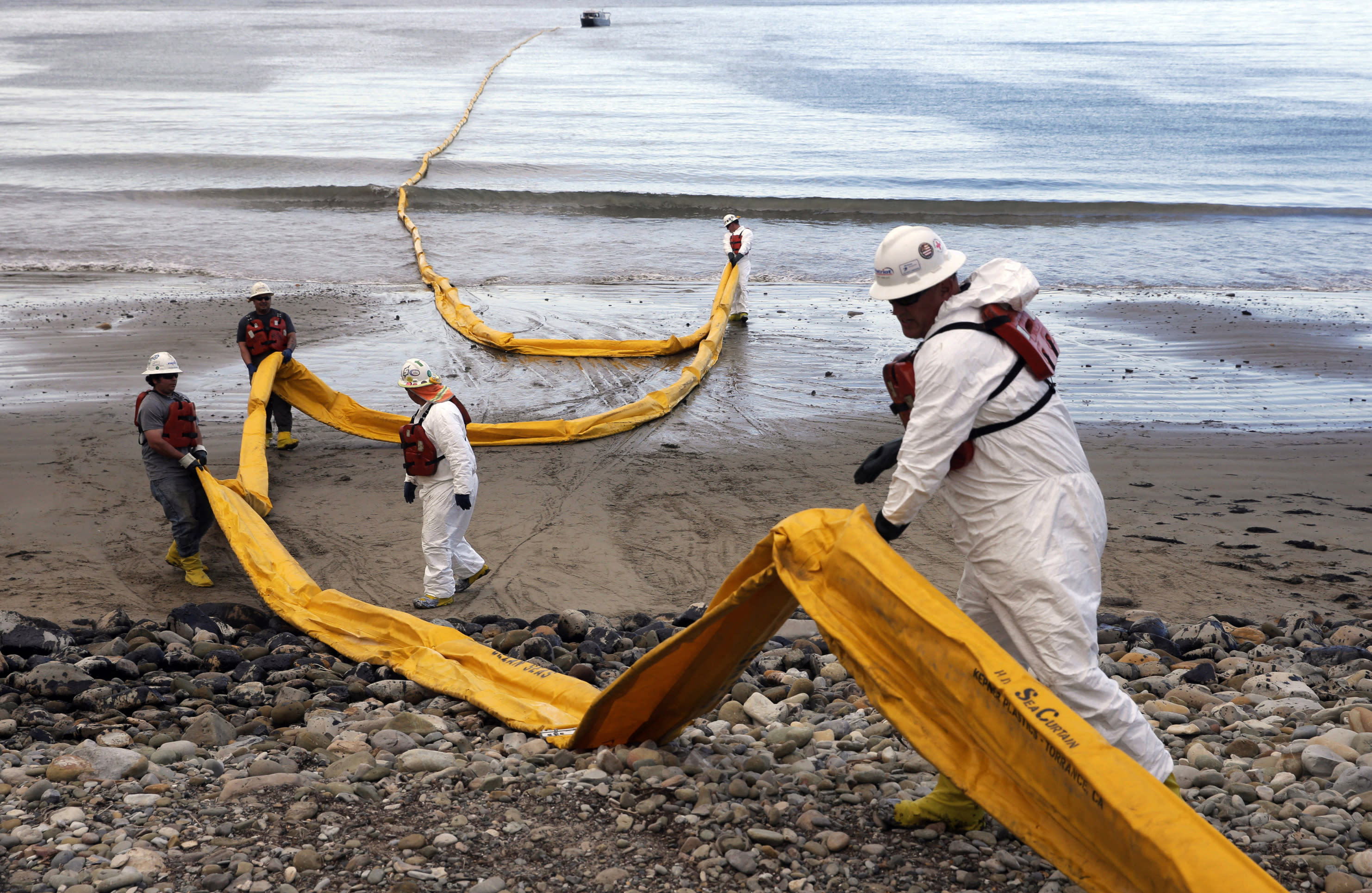 FILE - In this May 21, 2015, file photo, workers prepare an oil containment boom at Refugio State Beach, north of Goleta, Calif., two days after an oil pipeline ruptured, polluting beaches and killing hundreds of birds and marine mammals. California Gov. Gavin Newsom on Saturday, Oct. 12, 2019, signed a law intended to counter Trump administration plans to increase oil and gas production on protected public land. (AP Photo/Jae C. Hong, File)