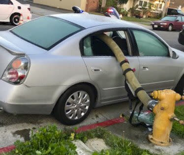 "This Feb. 26, 2019 photo provided by the Anaheim Fire and Rescue shows a car with a firehose running through the rear side windows in Anaheim, Calif. A California fire department enflamed some social media users but delighted others by posting pictures of the busted-out windows of a car that parked in front of a fire hydrant. In a Twitter thread posted Wednesday, the Anaheim Fire Department asked the public: ""Ever wonder what happens when a car is parked in front of a fire hydrant and a fire breaks out."" (Anaheim Fire and Rescue via AP)"