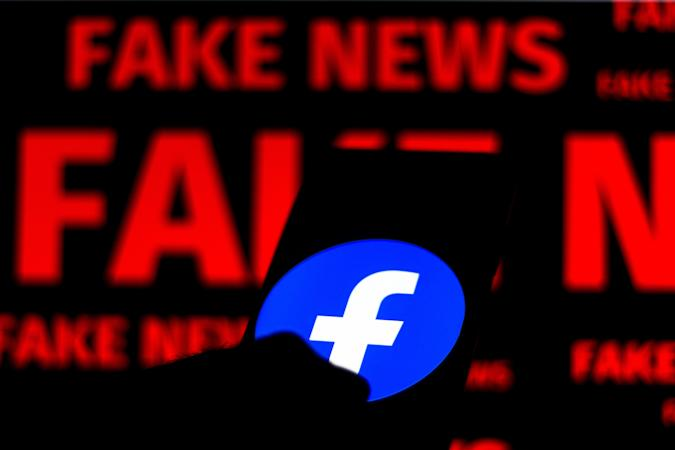 """BRAZIL - 2020/06/15: In this photo illustration the Facebook logo is displayed on a smartphone and a red alerting word """"FAKE NEWS"""" on the blurred background. (Photo Illustration by Rafael Henrique/SOPA Images/LightRocket via Getty Images)"""