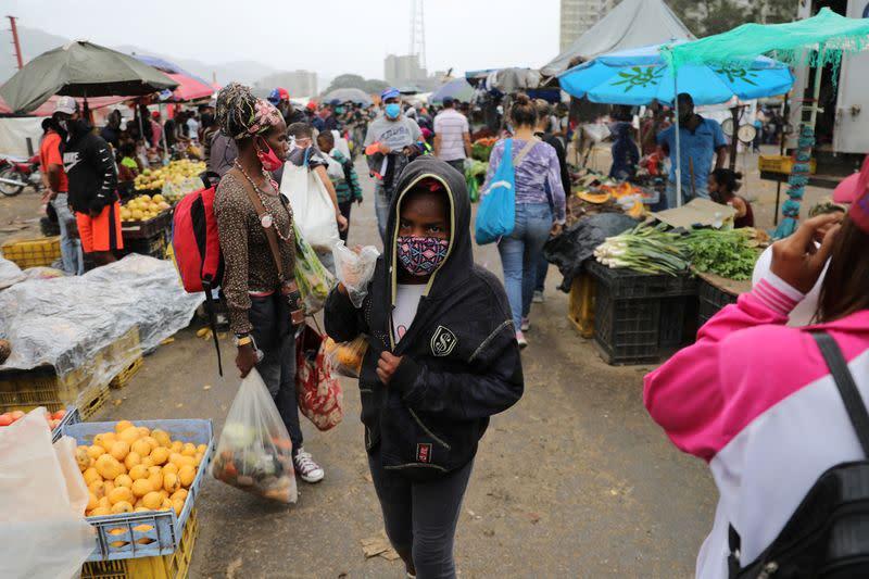 FILE PHOTO: A teenager walks at the Coche wholesale market amid coronavirus (COVID-19) disease outbreak in Caracas
