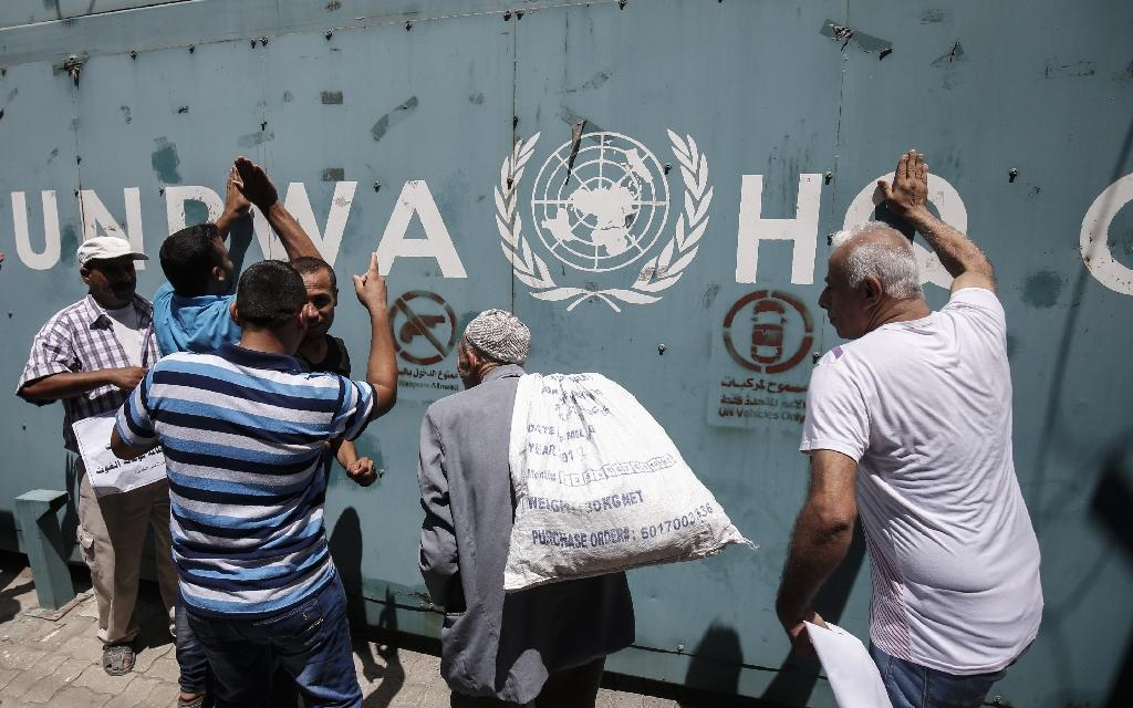UNRWA employees and their families protest against job cuts announced by the agency outside its offices in Gaza City on July 31, 2018 (AFP Photo/SAID KHATIB)