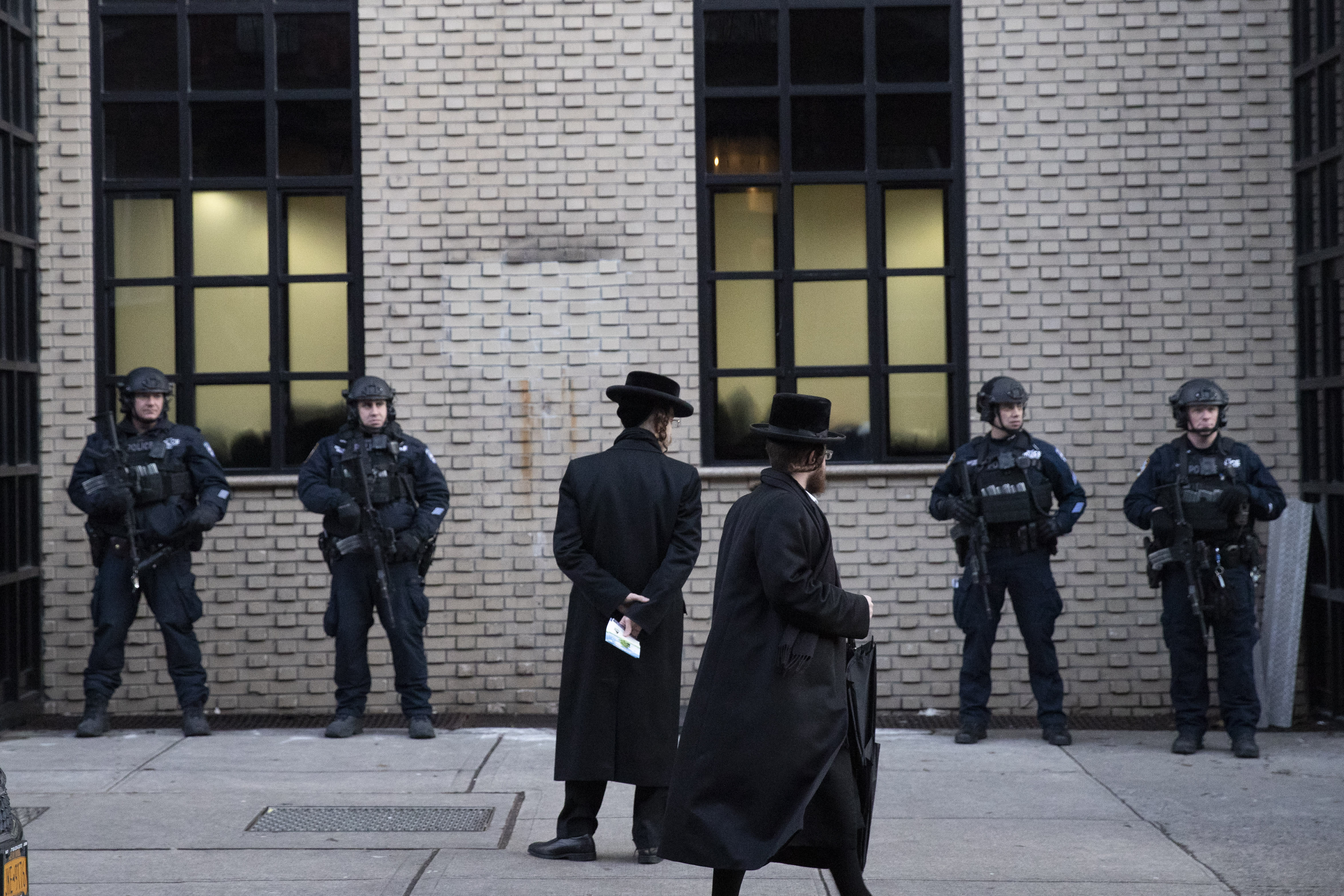 Orthodox Jewish men pass New York City police guarding a Brooklyn synagogue prior to a funeral for Mosche Deutsch, Wednesday, Dec. 11, 2019 in New York. Deutsch, a rabbinical student from Brooklyn, was killed Tuesday in the shooting inside a Jersey City, N.J. market. (AP Photo/Mark Lennihan)