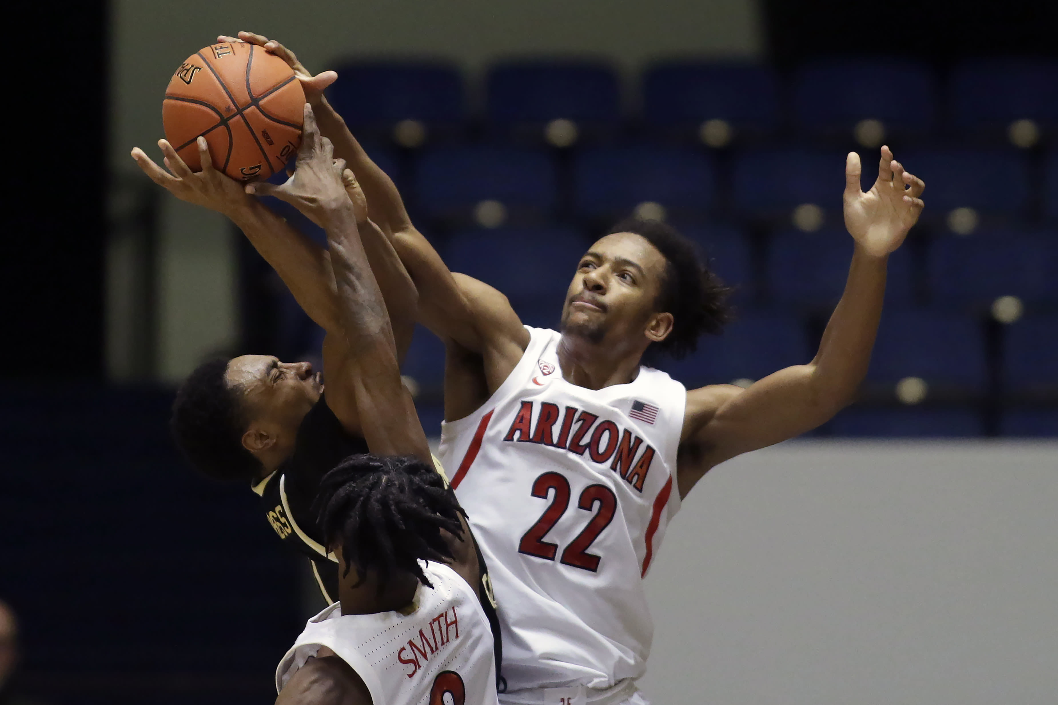 Arizona forward Zeke Nnaji, right, and guard Dylan Smith, bottom, block a shot by Wake Forest guard Brandon Childress, left, during the first half of an NCAA college basketball game at the Wooden Legacy tournament in Anaheim, Calif., Sunday, Dec. 1, 2019. (AP Photo/Alex Gallardo)