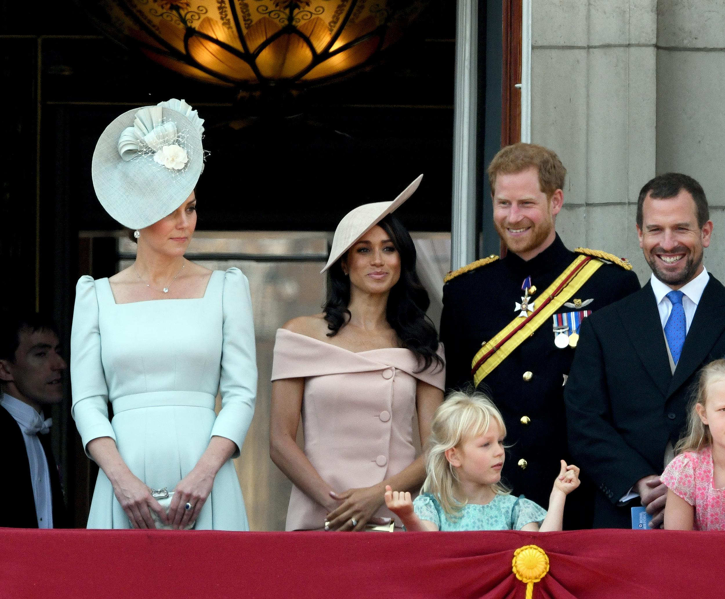 Catherine, Duchess of Cambridge, Meghan, Duchess of Sussex, Prince Harry, Duke of Sussex, Isla Phillips and Peter Phillips stand on the balcony of Buckingham Palace in London during Trooping the Colour