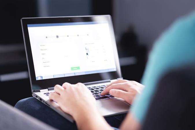 Man typing on laptop.