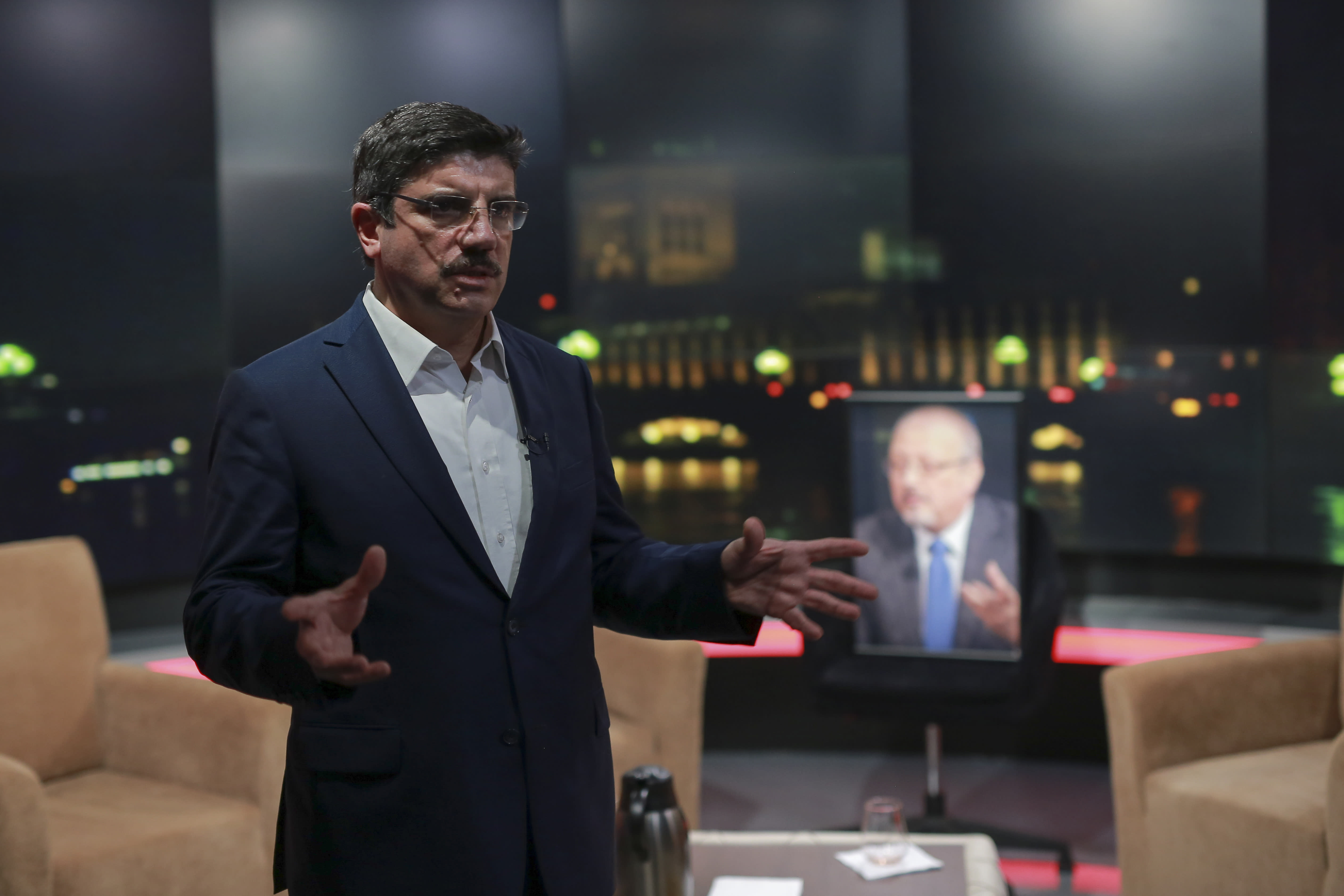 Yasin Aktay, an advisor to Turkey's President Recep Tayyip Erdogan and a good friend of Jamal Khashoggi, speaks to The Associated Press next to an empty chair with a picture of Saudi writer Jamal Khashoggi placed on it, before a live television program for London-based TV station al-Hewar, in Istanbul, late Thursday, Oct. 11, 2018. Khashoggi was supposed to appear on the show. The TV presenter Azzam Tamimi, a prominent Palestinian and a good friend of Khashoggi, told The Associated Press that the program was planned to discuss his new projects, his books and other issues. (AP Photo/Mucahid Yapici)