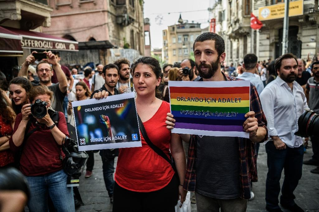 """People hold signs reading """"Justice for Orlando"""" during a rally staged by the LGBT community on Istiklal avenue in Istanbul on June 19, 2016 (AFP Photo/Ozan Kose)"""