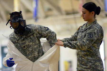 Pfc. Kaiya Capuchino from U.S. Army Medical Research Institute of Infectious Diseases (USAMRIID) trains US Army soldiers from the 101st Airborne Division (Air Assault), who are earmarked for the fight against Ebola, before their deployment to West Africa, at Fort Campbell, Kentucky October 9, 2014. REUTERS/Harrison McClary