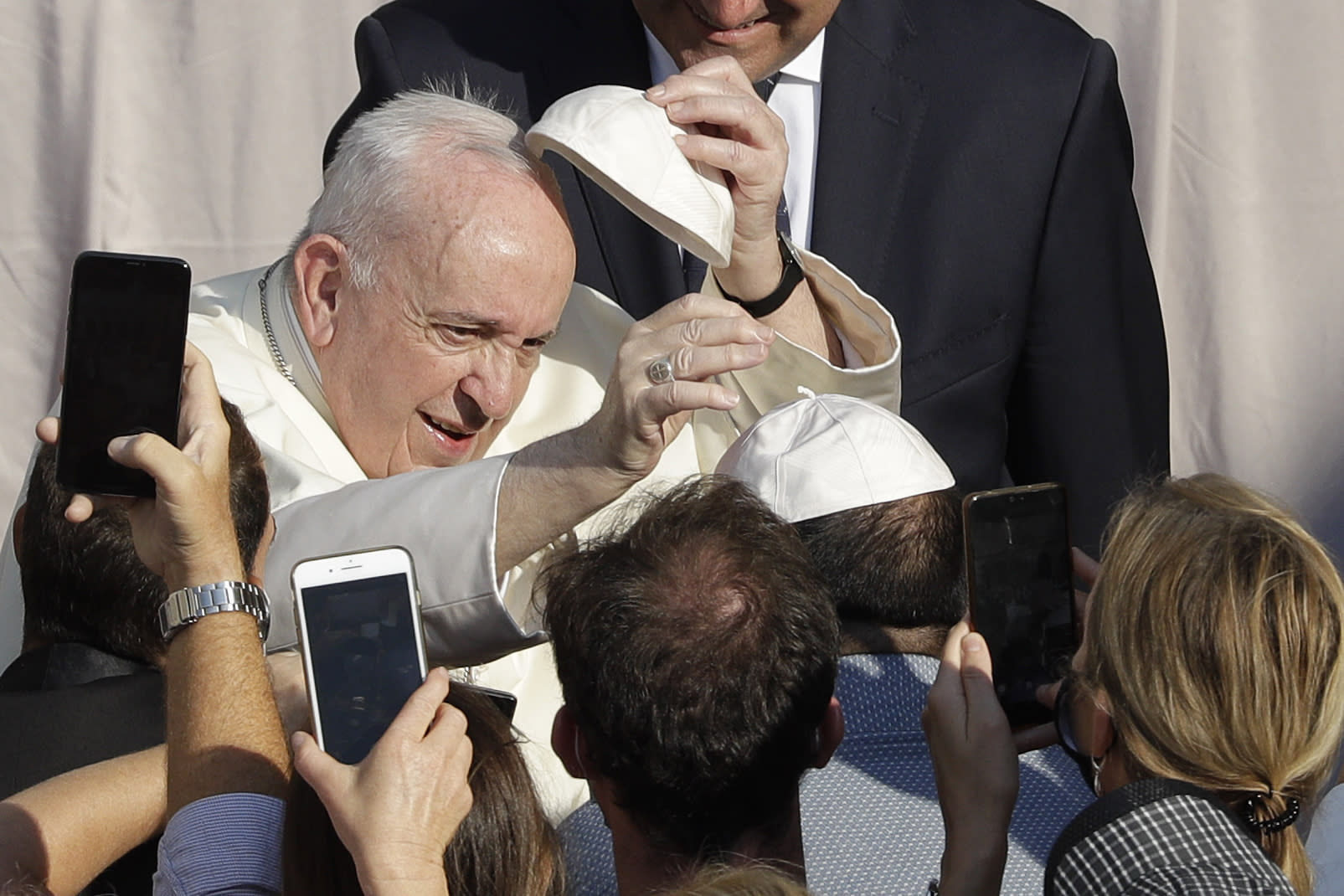 Pope Francis exchanges a skull cap which was donated by faithful as he arrives in the St. Damaso courtyard on the occasion of his weekly general audience at the Vatican, Wednesday, Sept. 16, 2020. (AP Photo/Gregorio Borgia)