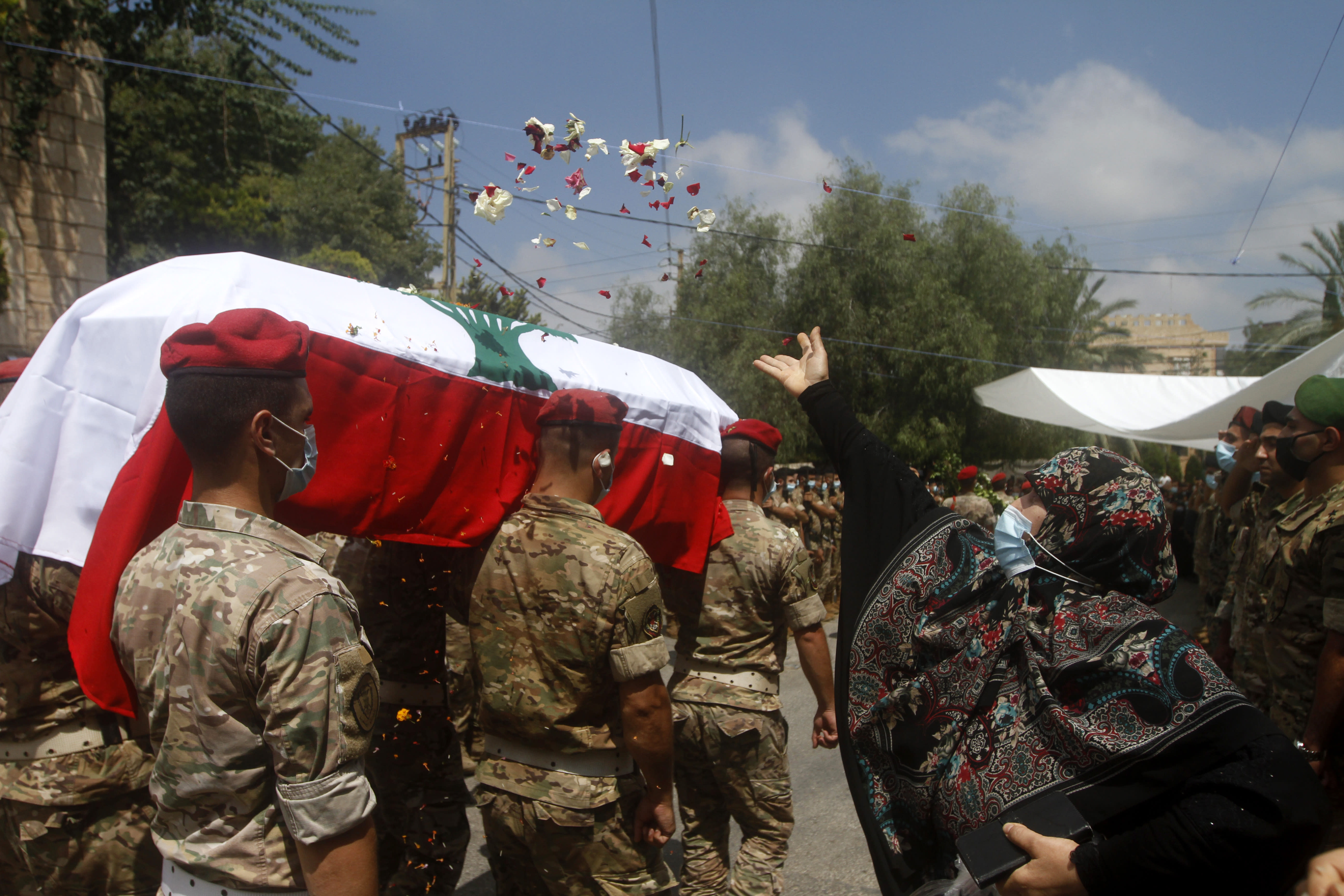 A woman throws flowers over Lebanese army soldiers who carry the coffin of lieutenant Ayman Noureddine, who was killed by Tuesday's explosion that hit the seaport of Beirut, during his funeral procession, in Numeiriyeh village, south Lebanon, Friday, Aug. 7, 2020. Rescue teams were still searching the rubble of Beirut's port for bodies on Friday, nearly three days after a massive explosion sent a wave of destruction through Lebanon's capital. (AP Photo/Mohammed Zaatari)