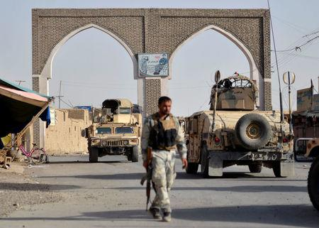 An Afghan security guard walks during a Taliban attack in Ghazni city, Afghanistan August 12, 2018. REUTERS/Stringer