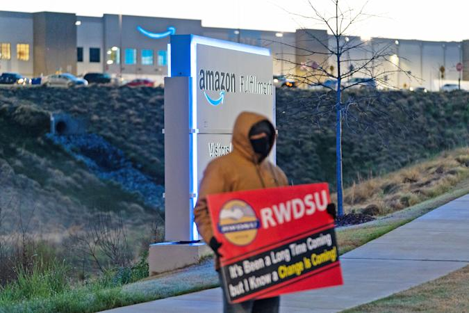 A worker pickets out front of an Amazon Fulfillment center.