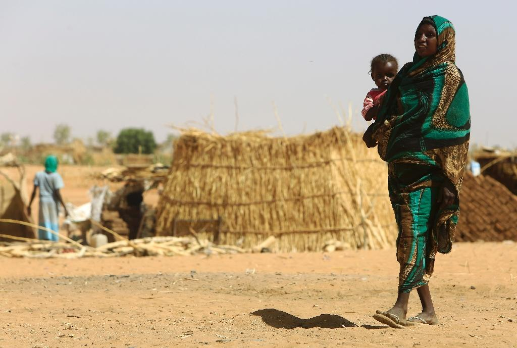 A Sudanese woman carries a baby at the Zamzam camp for Internally Displaced People (IDP), North Darfur, on April 9, 2015 (AFP Photo/Ashraf Shazly)