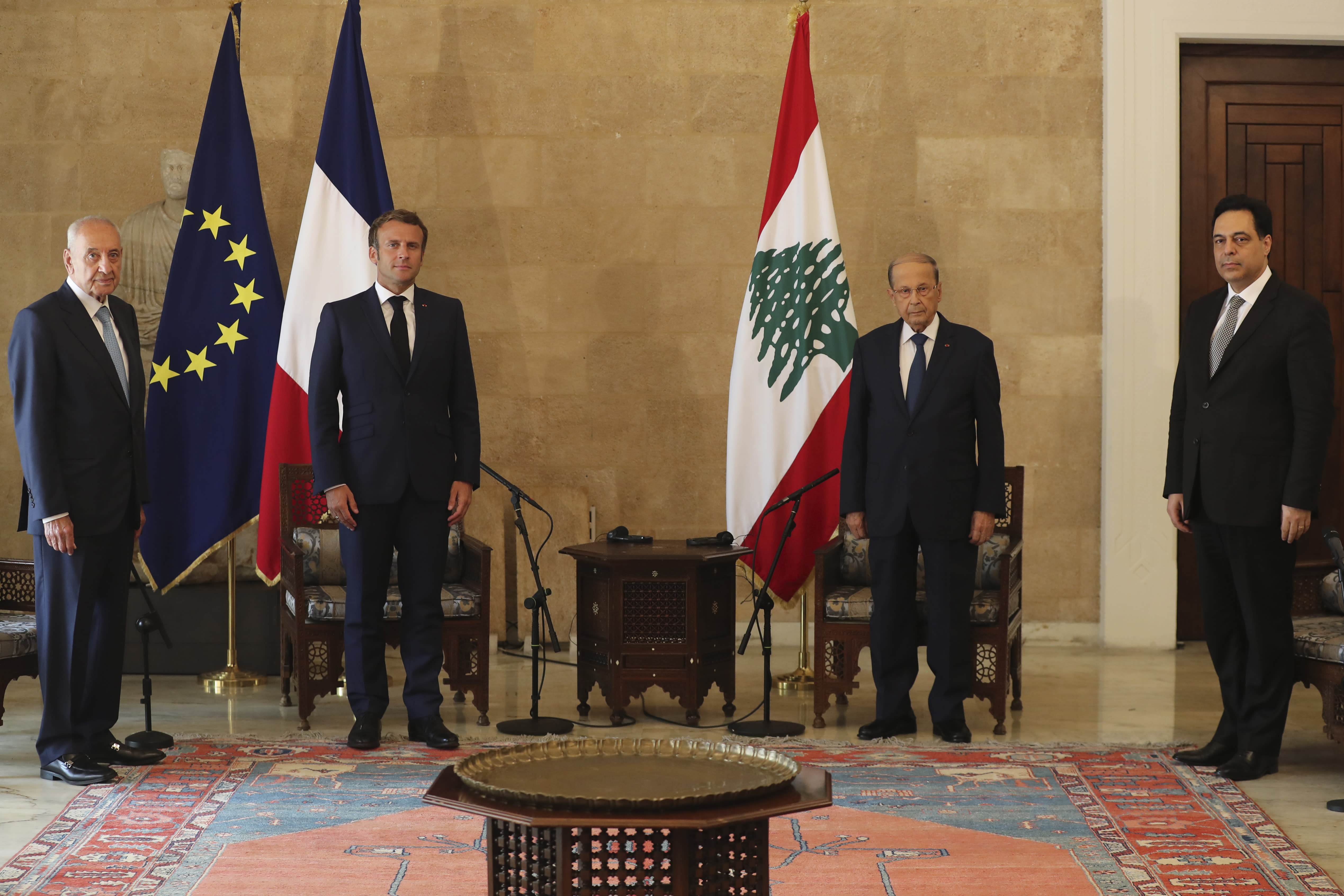 FILE - In this Aug.6, 2020 file photo, French President Emmanuel Macron, second left, and Lebanese President Michel Aoun, second right, meet at Beirut–Rafic Hariri International Airport, in Lebanon. In the wake of Beirut's massive port explosion, Macron has taken a tough line, setting deadlines for Lebanon's politicians to carry out reforms. His hands-on approach has angered some in Lebanon and brought praise from others. (AP Photo/Thibault Camus, Pool, File)