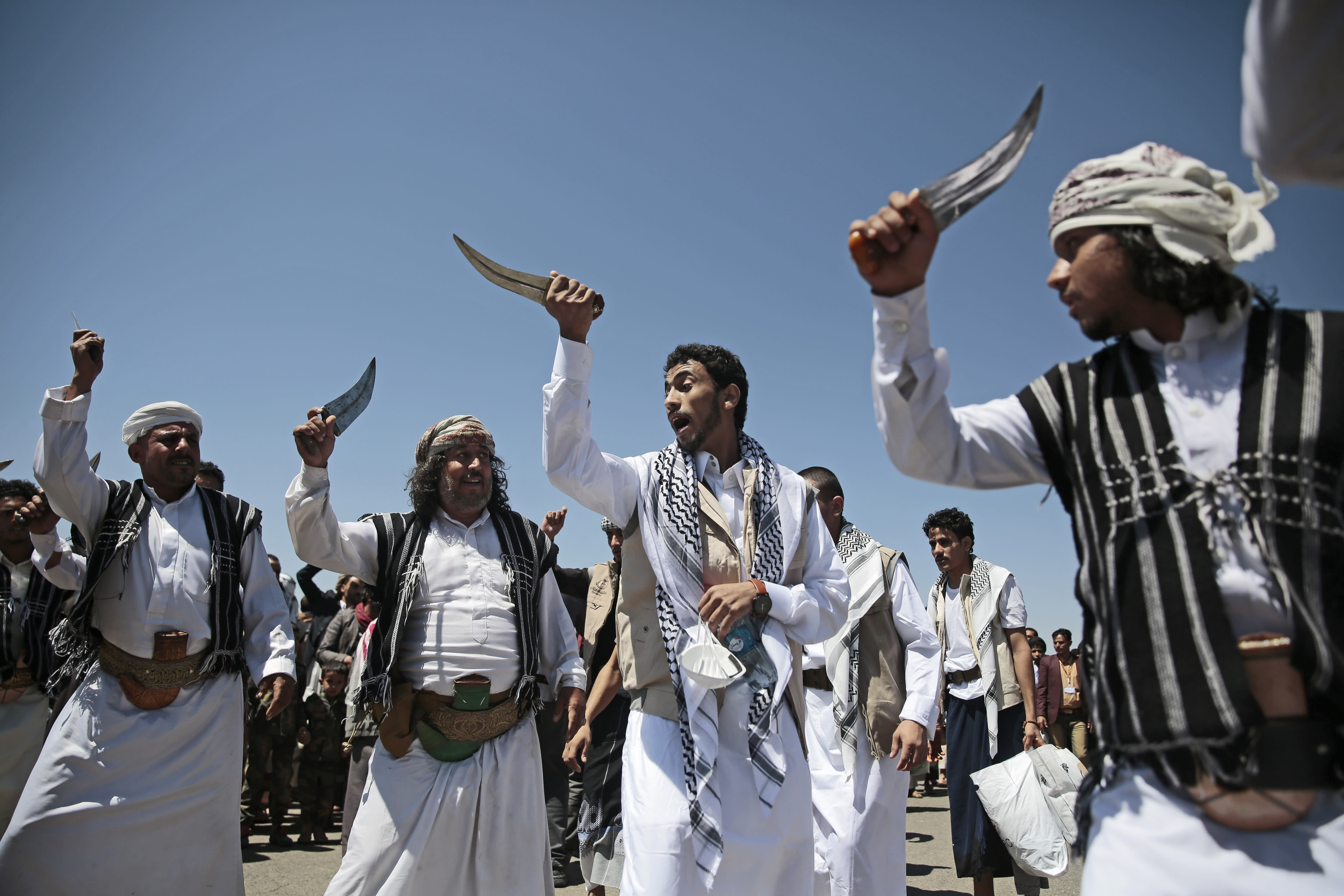 A Yemeni prisoner, center, performs a traditional dance during his arrival after being released by the Saudi-led coalition at the airport in Sanaa, Yemen, Friday, Oct. 16, 2020. Yemen's warring sides completed a major, U.N.-brokered prisoner swap on Friday, officials said, a development that could revive the country's stalled peace process after more than five years of grinding conflict. (AP Photo/Hani Mohammed)