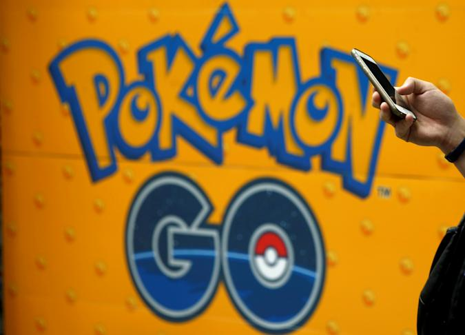 A man uses a mobile phone in front of an advertisement board bearing the image of Pokemon Go at an electronic shop in Tokyo, Japan, July 27, 2016.   REUTERS/Kim Kyung-Hoon/File Photo