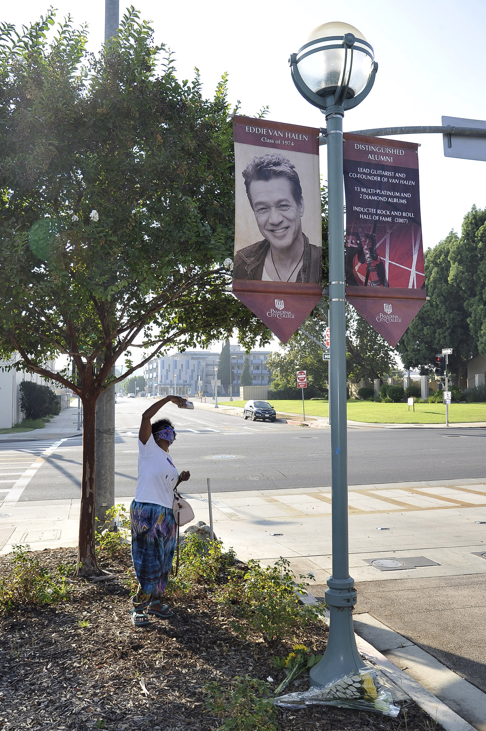Daniel Gaither, of Pasadena, photographs a banner acknowledging distinguished Pasadena City College alumnus Eddie Van Halen, Tuesday, Oct. 6, 2020, at the college in Pasadena, Calif. Van Halen, who had battled cancer, died Tuesday at age 65. (Richard Shotwell/Invision/AP)