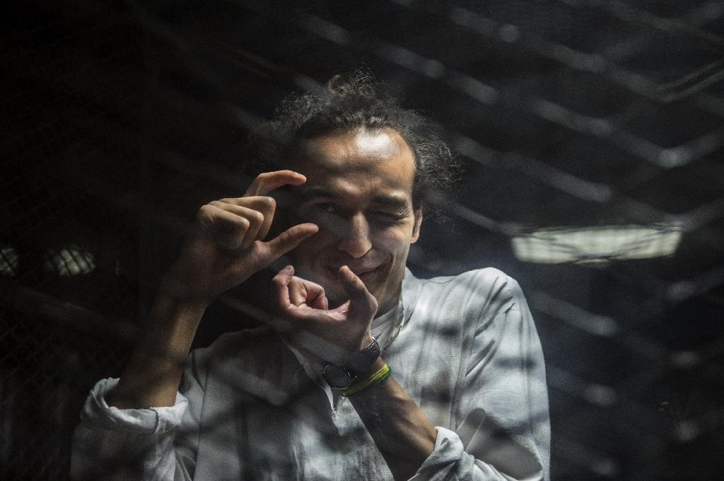 Egyptian photographer Mahmoud Abdel Shakour, known as Shawkan, gestures from inside a soundproof glass dock, during his trial in Cairo on August 9, 2016 (AFP Photo/Khaled Desouki)