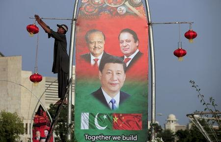 A man hangs decorations on a pole next to a banner showing Pakistan's President Hussain, China's President Xi and Pakistan's PM Sharif, ahead of Xi's visit to Islamabad