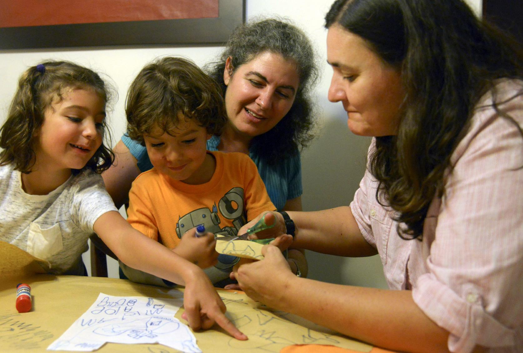 Colombian lesbian couple Ana Elisa Leiderman (2nd R) and Veronica Botero (R) watch as their daughter Raquel, 6, points at a sketch done by their son Ari, 4, both conceived by artificial insemination, at home in Medellin, Colombia, on August 26, 2014 (AFP Photo/Raul Arboleda)