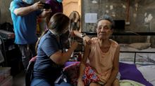Philippine health workers bring vaccines to the housebound in Manila suburb