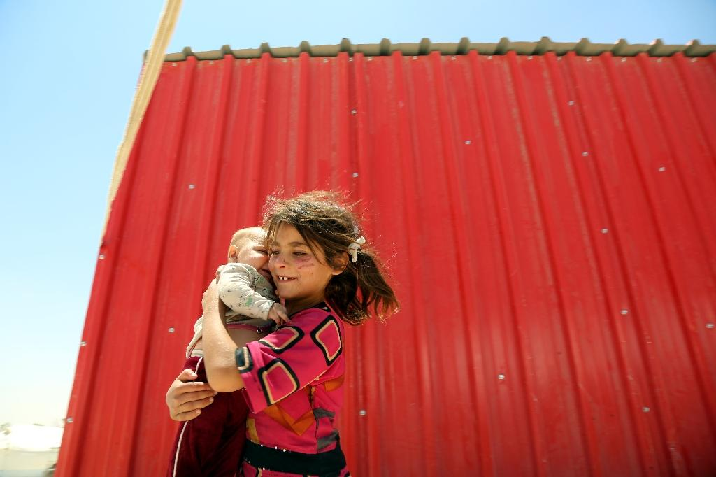 A displaced Syrian girl carries a baby on June 10, 2017 at a temporary camp in the northern Syrian village of Ain Issa, where many people who fled the Islamic State group stronghold of Raqa are taking shelter (AFP Photo/DELIL SOULEIMAN)