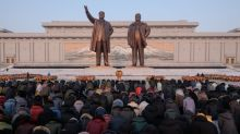North Koreans pay tribute to Kim's father in freezing cold