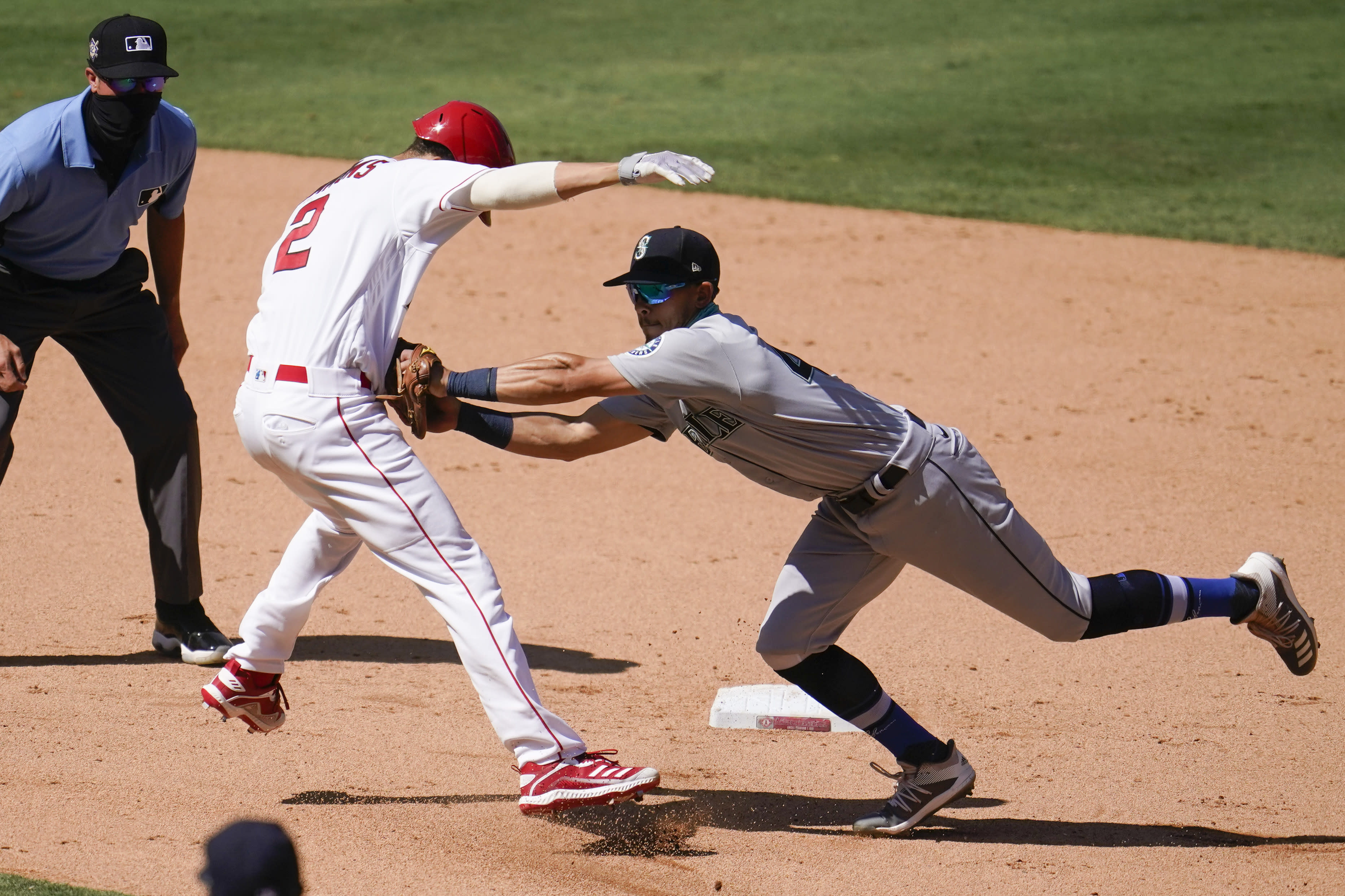 Los Angeles Angels' Andrelton Simmons, front left, is tagged out by Seattle Mariners third baseman Sam Haggerty in a rundown between first and second base during the seventh inning of a baseball game Sunday, Aug. 30, 2020, in Anaheim, Calif. Simmons drove in Albert Pujols with a single on the play. (AP Photo/Marcio Jose Sanchez)