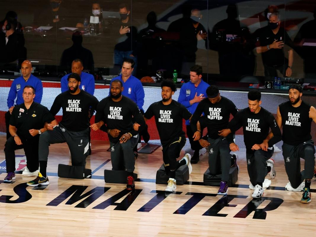 Players from the Los Angeles Lakers take a knee during the national anthem before the start of a game against the Portland Trail Blazers in Game Four of the Western Conference First Round during the 2020 NBA Playoffs at AdventHealth Arena at ESPN Wide Wor