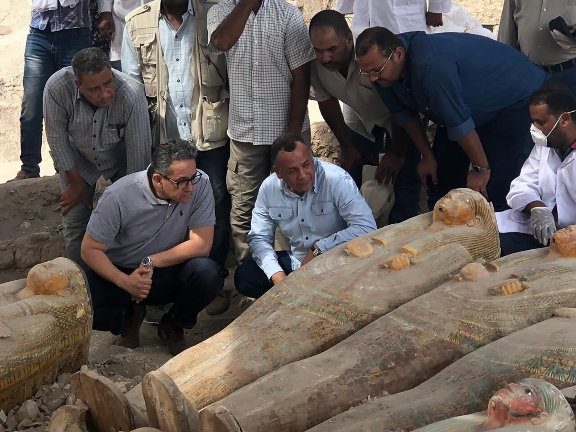 FILE - This Tuesday, Oct. 15, 2019 file photo provided by the Egyptian Ministry of Antiquities shows Egyptian Minister of Antiquities Khaled el-Anany, foreground left, looking at recently discovered ancient colored coffins with inscriptions and paintings, in the southern city of Luxor, Egypt. (Egyptian Ministry of Antiquities via AP, File)
