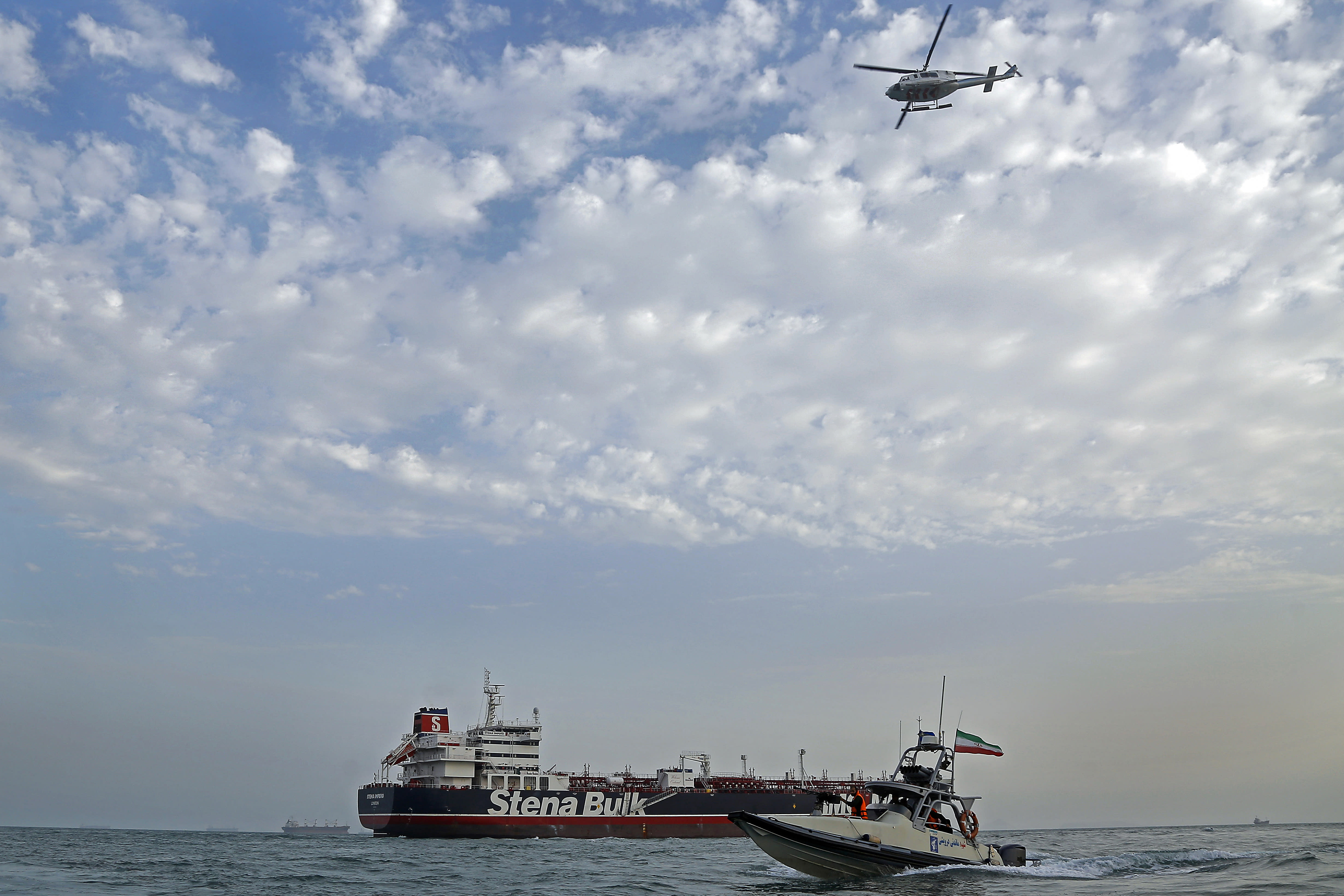 A speedboat and a helicopter of the Iran's Revolutionary Guard move around a British-flagged oil tanker Stena Impero which was seized on Friday by the Guard, in the Iranian port of Bandar Abbas, Sunday, July 21, 2019. Iranian officials say the seizure of the British oil tanker was a justified response to Britain's role in impounding an Iranian supertanker two weeks earlier off the coast of Gibraltar, a British territory located on the southern tip of Spain. (Hasan Shirvani/Mizan News Agency via AP)