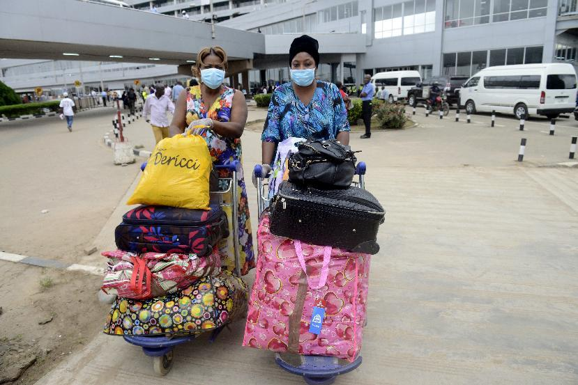 Passengers, wearing protective face masks and hand gloves push trolleys upon arrival at the Murtala Mohammed Airport in Lagos on August 11, 2014
