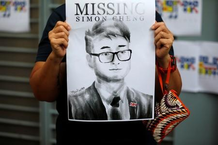 A woman holds a poster of Simon Cheng, a staff member at the consulate who went missing on August 9 after visiting the neighbouring mainland city of Shenzhen, during a protest outside the British Consulate-general office in Hong Kong
