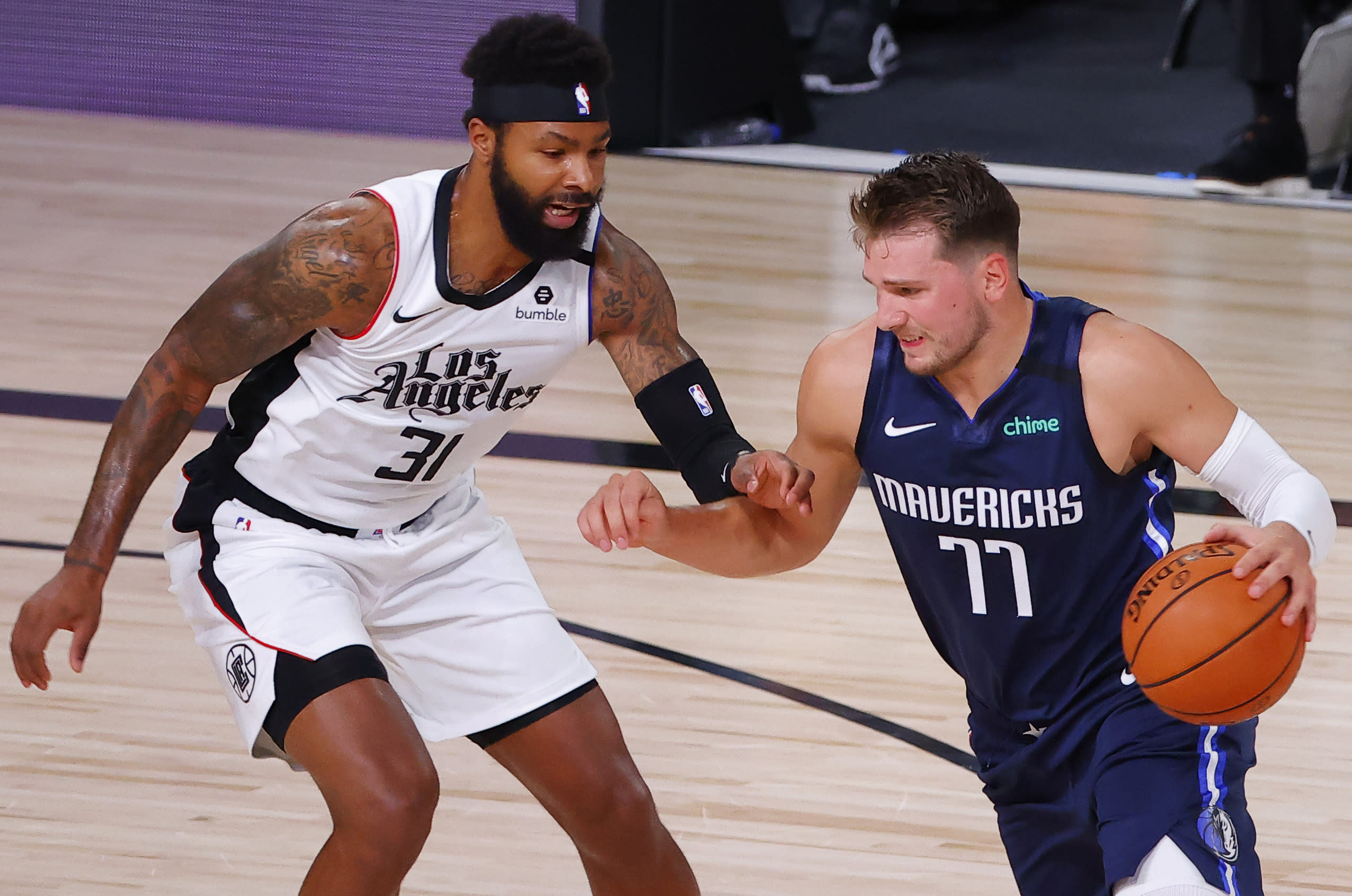Dallas Mavericks' Luka Doncic (77) drives against Los Angeles Clippers' Marcus Morris Sr. (31) during the first quarter of Game 4 of an NBA basketball first-round playoff series, Sunday, Aug. 23, 2020, in Lake Buena Vista, Fla. (Kevin C. Cox/Pool Photo via AP)