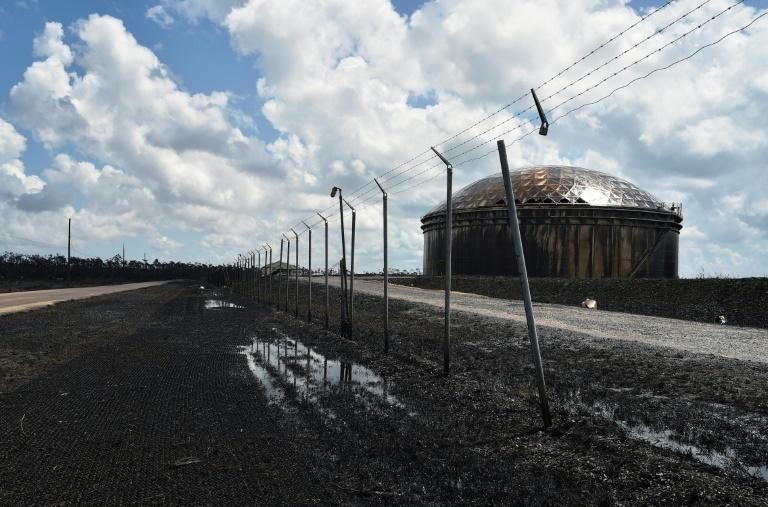 Several huge oil storage tanks are colored black by overflowing oil, which has spread over a still yet-to-be-defined section of land near the coast (AFP Photo/Leila MACOR)