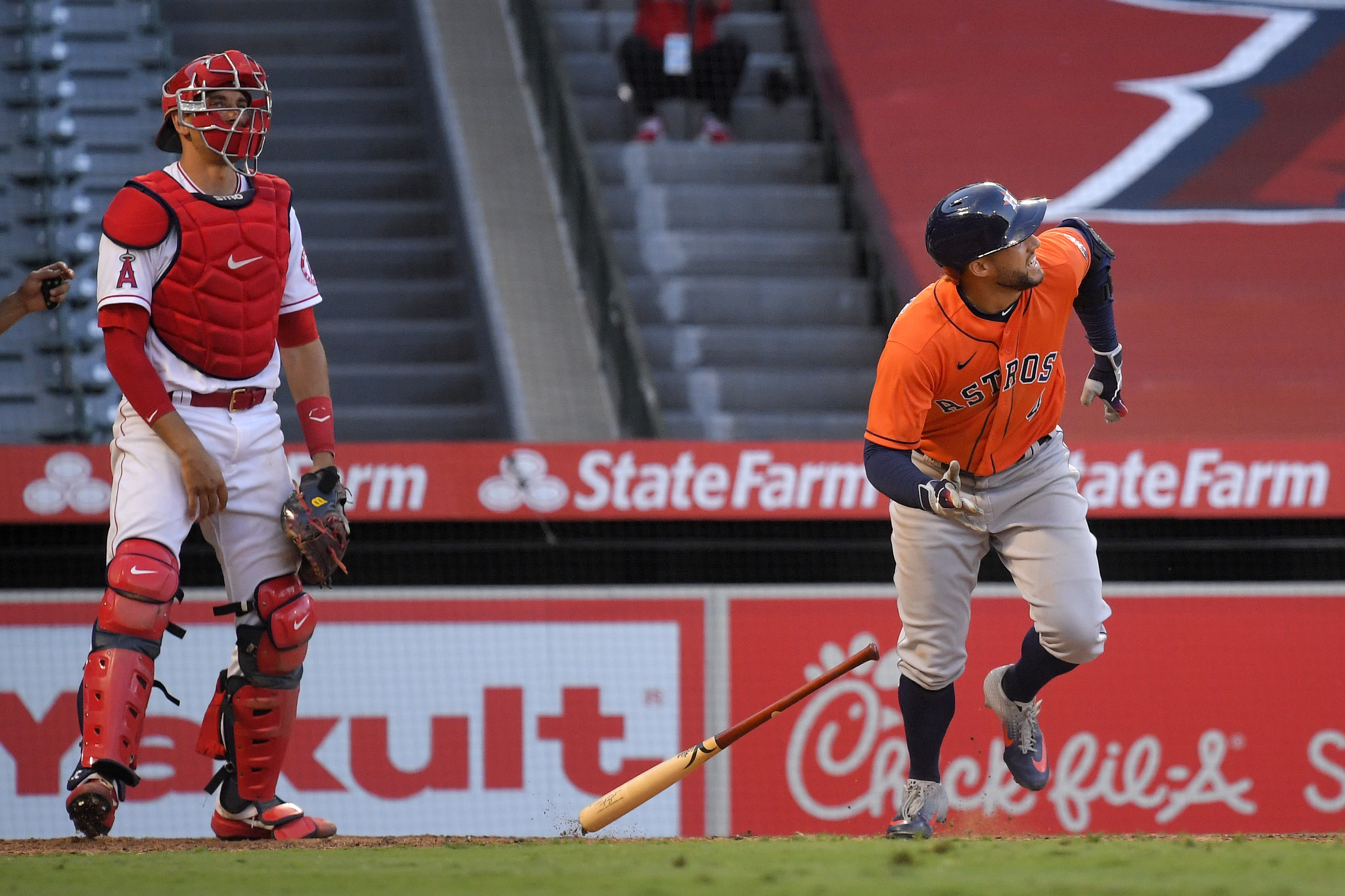 Houston Astros' George Springer runs to first after hitting a two-run home run, next to Los Angeles Angels catcher Max Stassi during the ninth inning of a baseball game Saturday, Aug. 1, 2020, in Anaheim, Calif. (AP Photo/Mark J. Terrill)