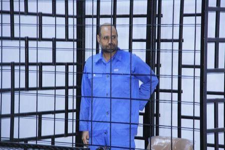 Saif al-Islam Gaddafi, son of late Libyan leader Muammar Gaddafi, attends a hearing behind bars in a courtroom in Zintan