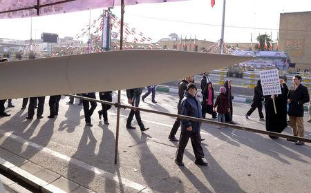 FILE PHOTO: People walk near an Iranian-made missile during a ceremony marking the 37th anniversary of the Islamic Revolution, in Tehran February 11, 2016. REUTERS/Raheb Homavandi/File Photo