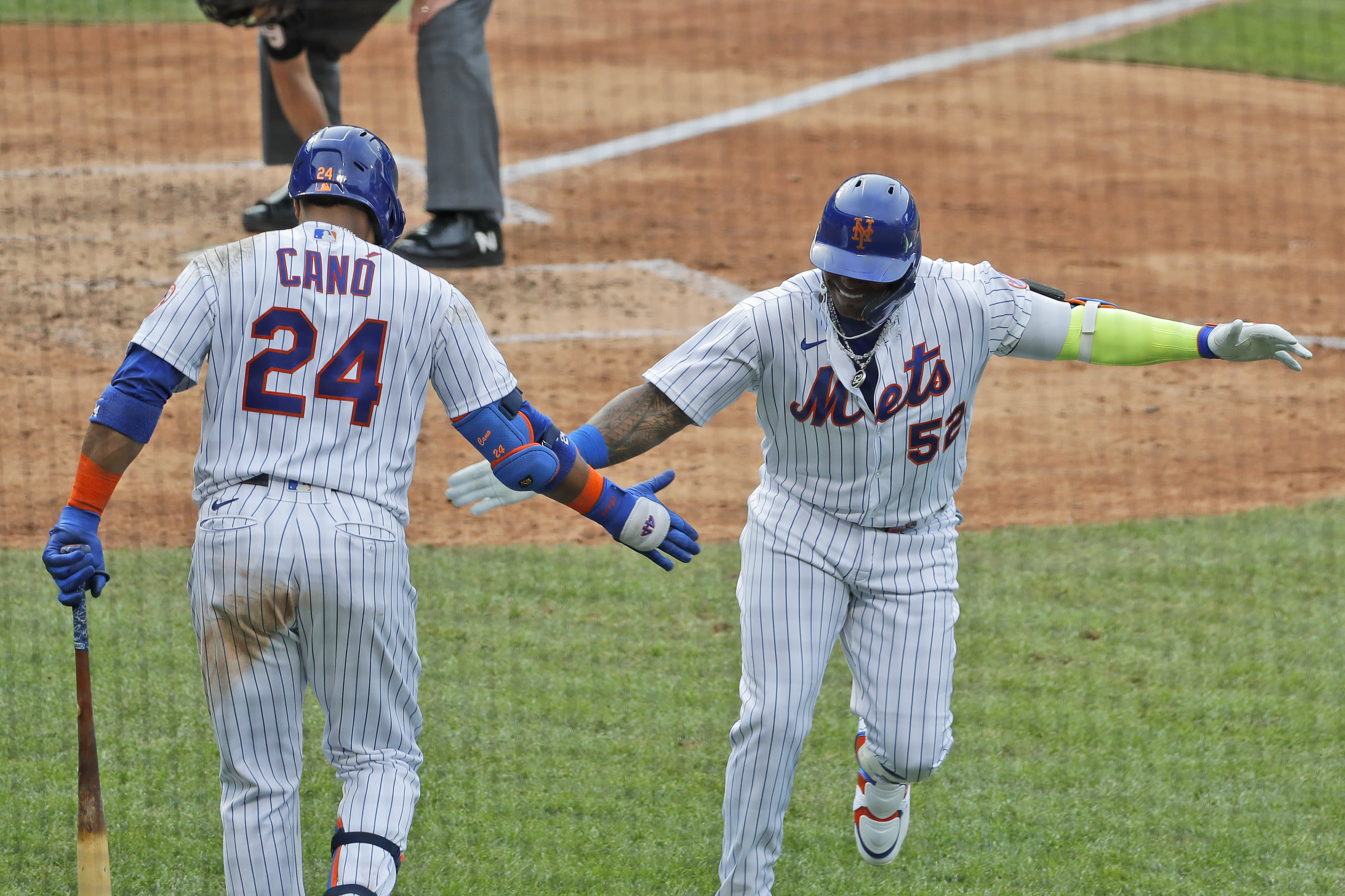 New York Mets' Yoenis Cespedes, right, celebrates his solo home run with Robinson Cano (24) during the seventh inning of a baseball game against the Atlanta Braves at Citi Field, Friday, July 24, 2020, in New York. (AP Photo/Seth Wenig)