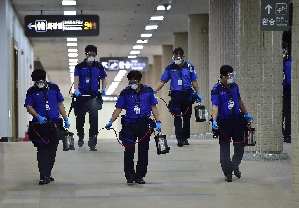 Workers spray antiseptic solution at the customs, immigration and quarantine office of Seoul's Gimpo international airport during the MERS outbreak on June 17, 2015 (AFP Photo/Jung Yeon-Je)