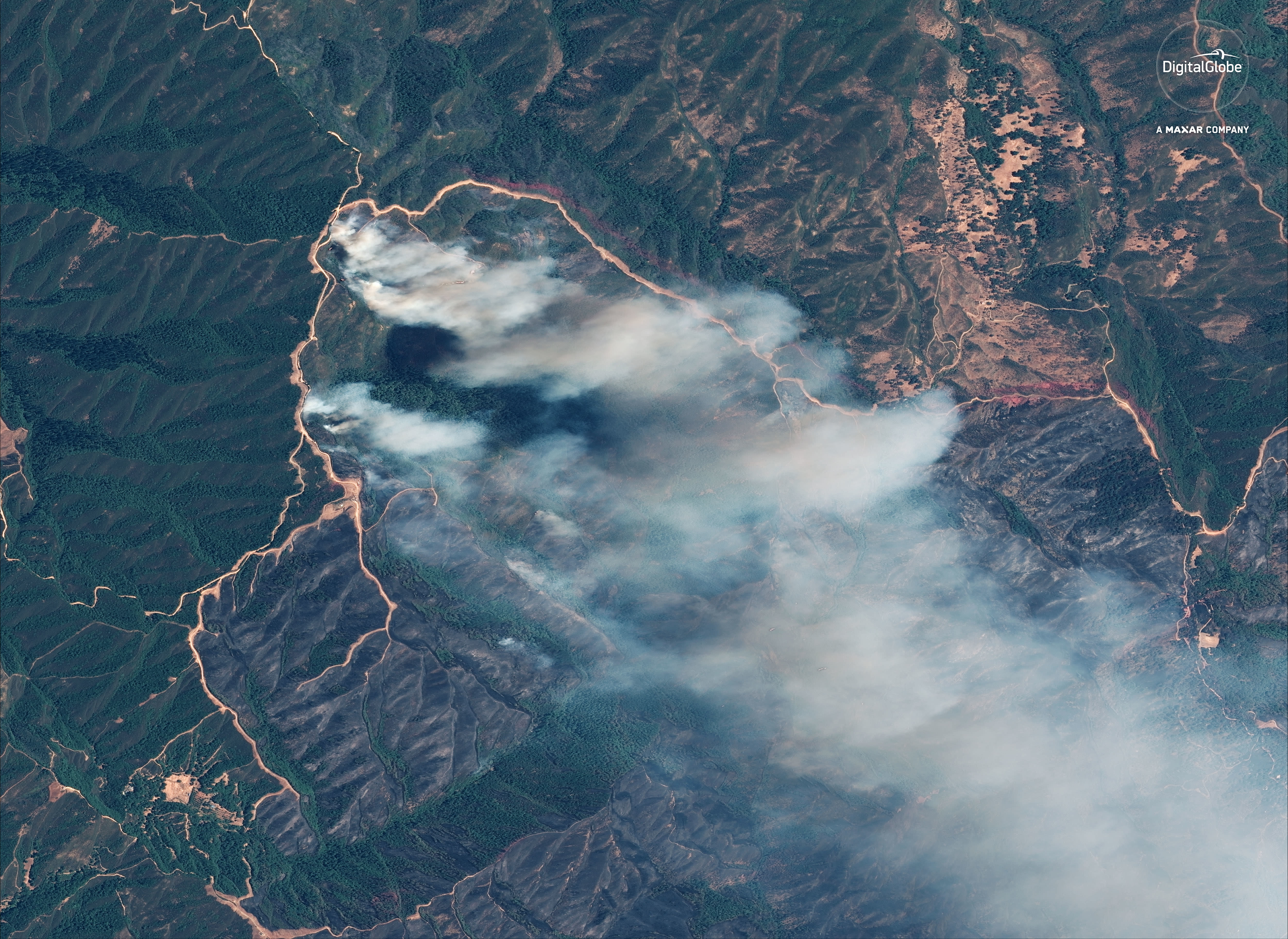 """This Aug. 6, 2018 satellite image provided by DigitalGlobe shows plumes of smoke from the """"River Fire"""" burning vegetation west of Clear Lake, Calif. The dark brown areas at center, encircled by lighter-colored bulldozed trails, shows burned vegetation around the South Cow Mountain recreation area. (Satellite Image ©2018 DigitalGlobe, a Maxar company, via AP)"""