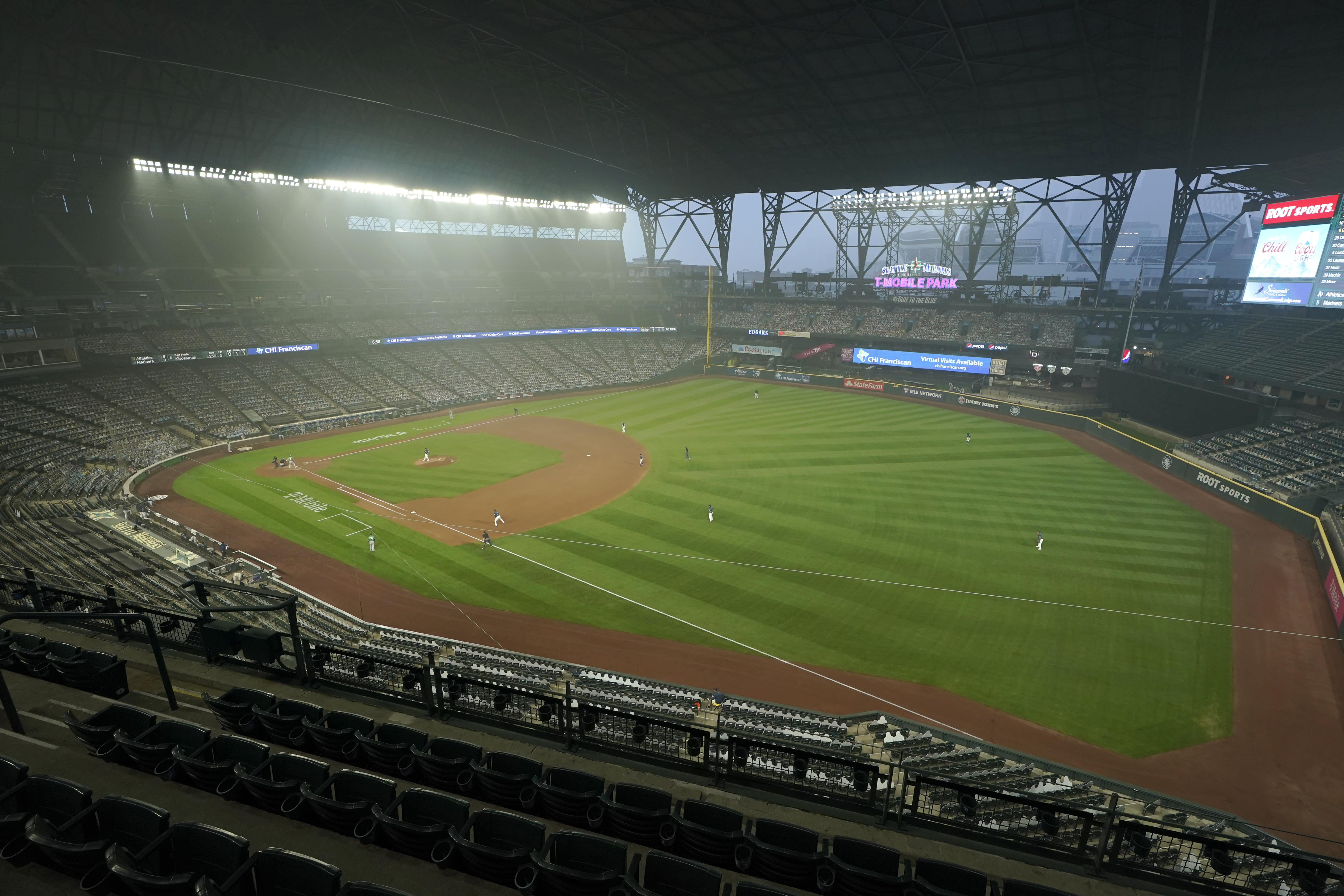 Smoke from wildfires fills the air at T-Mobile Park as the Seattle Mariners and the Oakland Athletics play with the roof extended during the sixth inning of the second baseball game of a doubleheader, Monday, Sept. 14, 2020, in Seattle. (AP Photo/Ted S. Warren)