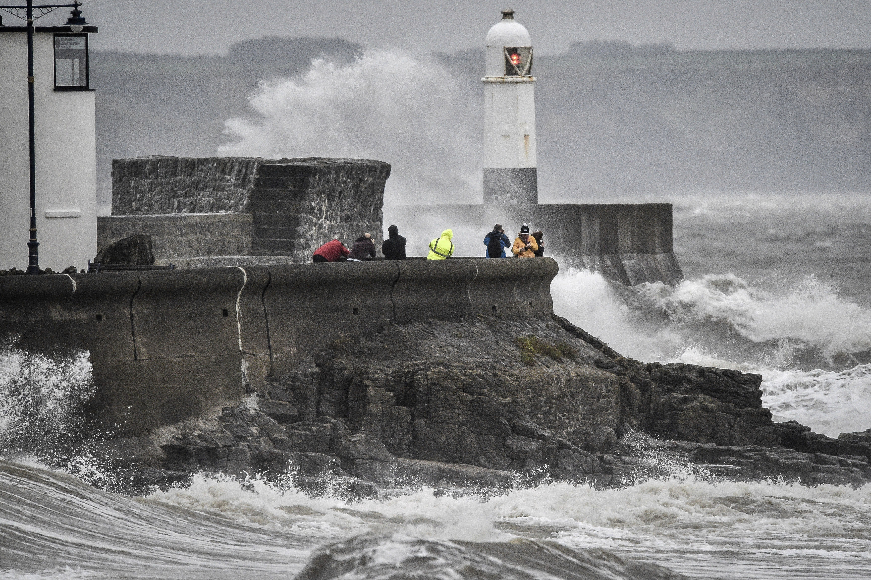 People watch as waves crash against the harbour wall, in Porthcawl, South Wales, Saturday, Oct. 13, 2018. (Ben Birchall/PA via AP)
